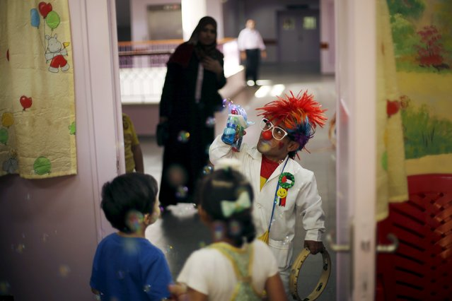 A Palestinian social activist working for the International South South Cooperation (Cooperazione Internazionale Sud Sud, or CISS) entertain children who are patients inside a hospital in Gaza City August 31, 2015. (Photo by Mohammed Salem/Reuters)