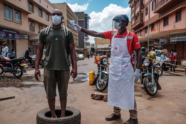 A Red Cross volunteer measures the temperature of a man before he can enter Nakasero market in Kampala, on April 1, 2020. Ugandan President Yoweri Museveni on March 30, 2020, ordered an immediate 14-day nationwide lockdown in a bid to halt the spread of the COVID-19 coronavirus which has so far infected 33 people in the country. (Photo by Sumy Sadurni/AFP Photo)
