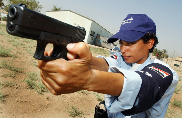 Female police recruit Aziza Ali, 30, aims her Glock 9mm pistol at a target on the gunnery range at the law enforcement academy July 18, 2004 in Baghdad, Iraq. (Photo by Wathiq Khuzaie)