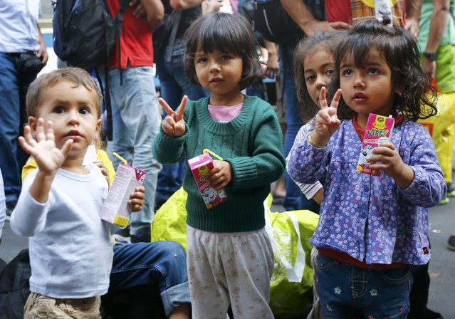 Migrants' children gesture near the Keleti railway station in Budapest, Hungary, September 3, 2015. Over 2,000 migrants, many of them refugees from conflicts in the Middle East and Africa, had been camped in front of the Keleti Railway Terminus, closed to them by authorities saying European Union rules bar travel by those without valid documents. (Photo by Leonhard Foeger/Reuters)