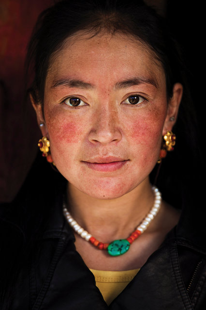 """China: """"Among the most graceful women I encountered, this Tibetan mother of two in a rural village looked like this the moment she opened her door to me. She had been cleaning her house, and yet she was wearing her jewellery"""". (Photo by Mihaela Noroc/The Guardian)"""