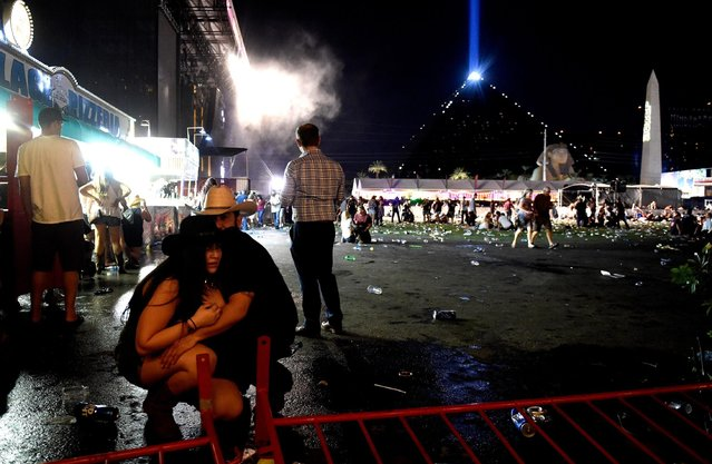 People take cover at the Route 91 Harvest country music festival after apparent gun fire was heard on October 1, 2017 in Las Vegas, Nevada. There are reports of an active shooter around the Mandalay Bay Resort and Casino. (Photo by David Becker/Getty Images)