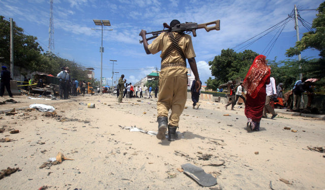 A Somali policeman walks towards the scene of an explosion outside the headquarters of Somalia's Criminal Investigation Department (CID) in the capital Mogadishu, July 31, 2016. (Photo by Ismail Taxta/Reuters)