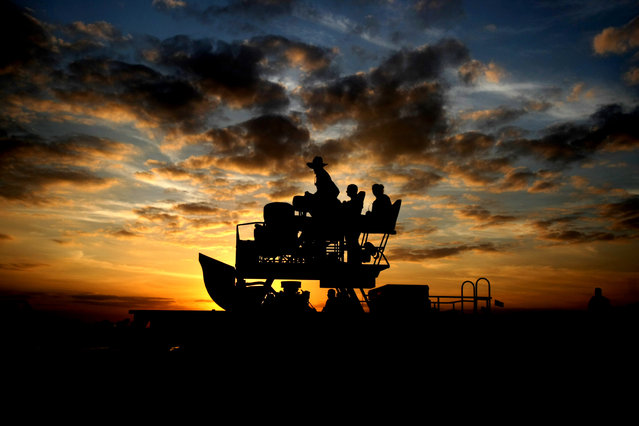 A swamp buggy is silhouetted as the sun sets. (Photo by Gary Coronado/The Palm Beach Post)