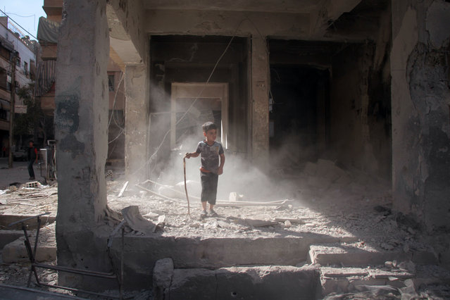 A Syrian boy stands amidst the rubble of a building in the rebel- held town of Douma, on the eastern outskirts of Damascus, on October 6, 2017 following reported air strikes by Syrian government forces. (Photo by Hamza Al-Ajweh/AFP Photo)