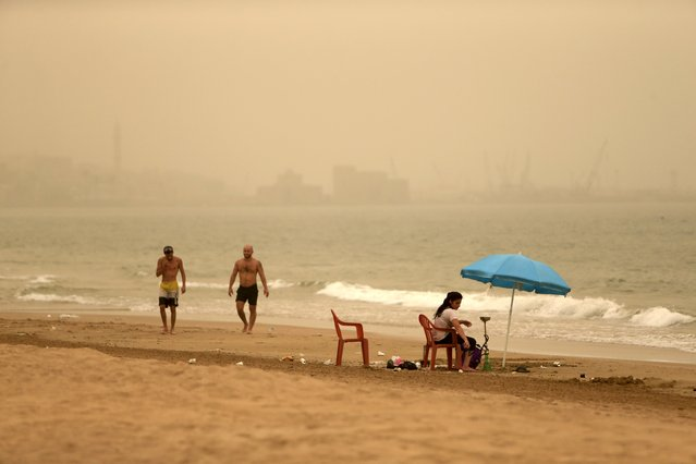 Men walk along the shore while a woman smokes a hookah, or water pipe, during a sandstorm near the sea castle of the port-city of Sidon, Lebanon September 8, 2015. (Photo by Ali Hashisho/Reuters)