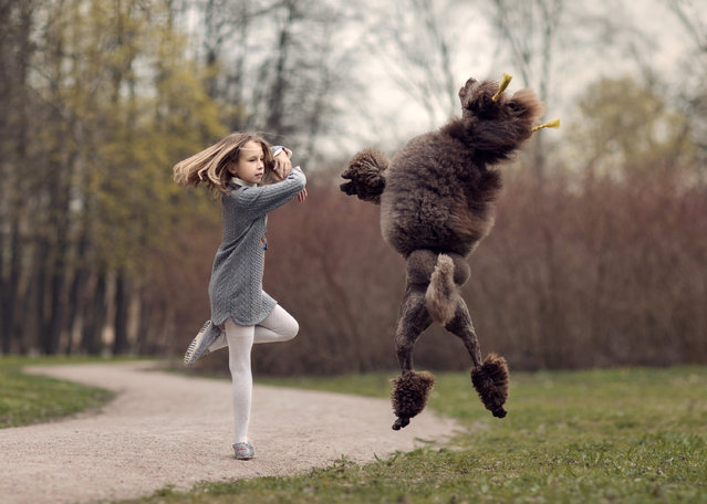 Nine year old Maria Palkina dancing with dogs. (Photo by Andrey Seliverstov/Caters News Agency)