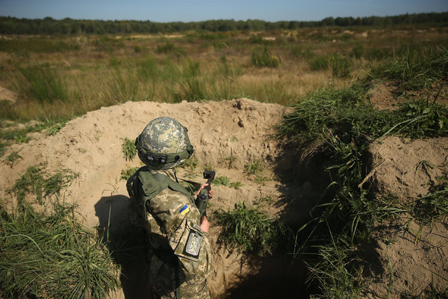 "A Ukrainian marine stands in a trench during training on the second day of the ""Rapid Trident"" NATO military exercises on September 16, 2014 near Yavorov, Ukraine. (Photo by Sean Gallup/Getty Images)"