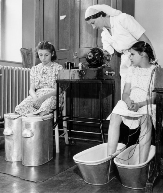 Two apprehensive looking girls with their feet in baths receive treatment from a nurse in Bristol health centre's orthopaedic department, July 1948. (Photo by Popperfoto/Getty Images)