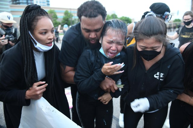 A young protester receives aid after being pepper sprayed during a peaceful demonstration near the Mobil gas station on S Washington Ave by the I-35W on-ramp during the sixth day of demonstrations in response to the death in Minneapolis police custody of George Floyd in Minneapolis, Minnesota, U.S. May 31, 2020. (Photo by Nicholas Pfosi/Reuters)