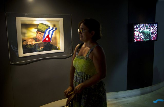 A visitor stands in front of a photo of Cuban leader Fidel Castro during an exhibition at the Diversity Hall in Old Havana, Cuba, Friday, August 12, 2016. Castro will mark his 90th birthday Saturday. (Photo by Ramon Espinosa/AP Photo)