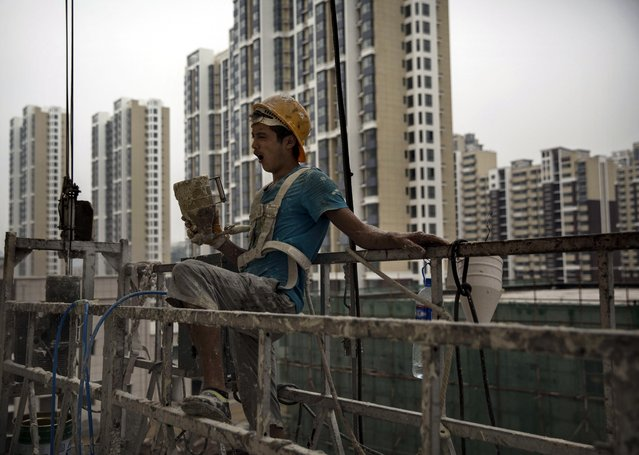 A Chinese construction worker yawns as he paints the exterior of a new apartment complex on August 29, 2014 in Beijing, China. (Photo by Kevin Frayer/Getty Images)