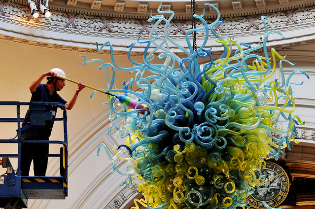 Victoria & Albert Museum technical service member Andy Monks cleans the Rotunda Chandelier by Dale Chihuly to complete the cleaning of the Dome in the Museum's Grand Entrance in Cromwell Road, west London, on October 2, 2014. (Photo by Nick Ansell/PA Wire)
