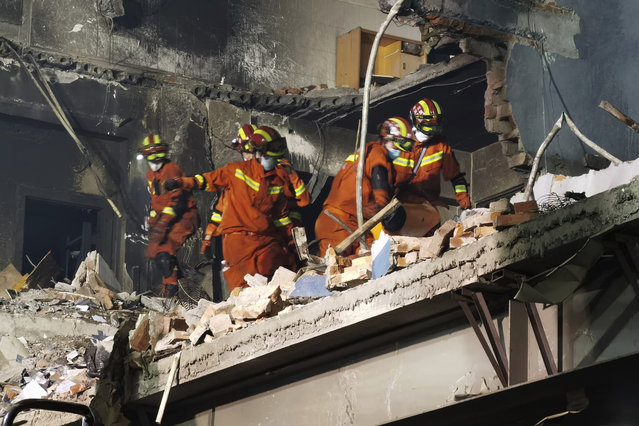 Firefighters look for victims in damaged buildings in the aftermath of a tanker truck explosion near a highway in Wenling in eastern China's Zhejiang province early Sunday, June 14, 2020. More than a dozen were killed and others injured after the tanker truck veered off the Shenyang-Haikou Expressway after the explosion. (Photo by Chinatopix via AP Photo)