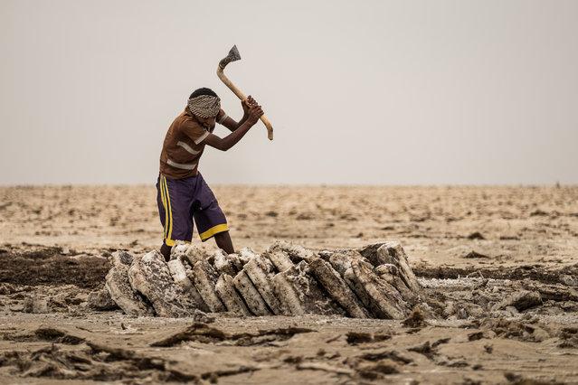 A man carving out salt blocks. (Photo by Joel Santos/Barcroft Images)