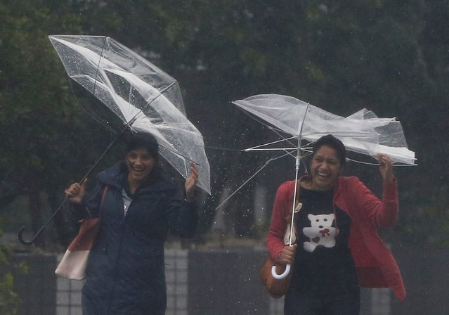 Passers-by with umbrellas struggle against strong winds and heavy rain caused by Typhoon Phanfone, in Tokyo October 6, 2014. Hundreds of flights were canceled and thousands of people advised to evacuate as a powerful typhoon lashed Japan on Monday with heavy rains and high winds, leaving at least one person dead as it headed towards Tokyo. (Photo by Issei Kato/Reuters)