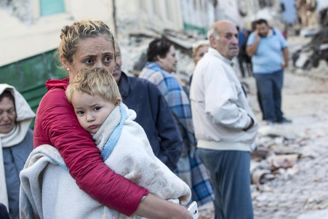 A mother embraces his son in Amatrice, central Italy, where a 6.1 earthquake struck just after 3:30 a.m., Italy, 24 August 2016. The quake was felt across a broad section of central Italy, including the capital Rome where people in homes in the historic center felt a long swaying followed by aftershocks. (Photo by Massimo Percossi/ANSA)