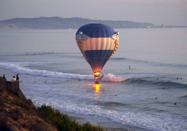 In this Sunday, October 5, 2014 photo provided by Jenny Parsons, a hot air balloon dips close to the ocean in Cardiff-by-the-Sea, a beach community in Encinitas, Calif. A man was proposing to his girlfriend during their sunset ride Sunday when the balloon drifted off course and hovered over the water, prompting a rescue by lifeguards and surfers. (Photo by Jenny Parsons/AP Photo)