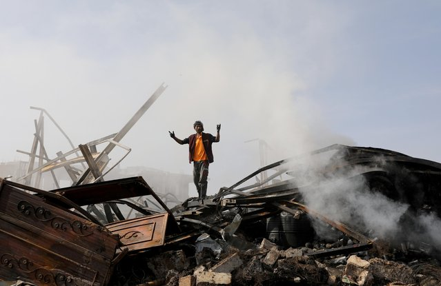 A worker reacts as he stands on the wreckage of a vehicle oil and tires store hit by Saudi-led air strikes in Sanaa, Yemen on July 2, 2020. (Photo by Khaled Abdullah/Reuters)