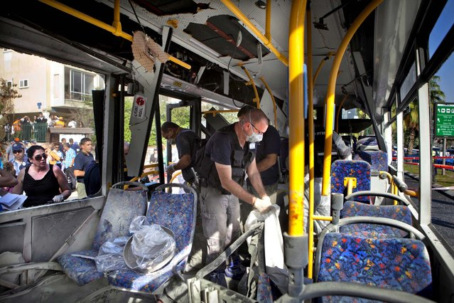 Israeli police officers examine a destroyed bus at the site of a bombing in Tel Aviv, Israel, November 21, 2012. A bomb ripped through an Israeli bus near the nation's military headquarters in Tel Aviv, wounding 16 people. (Photo by Dan Balilty/Associated Press)