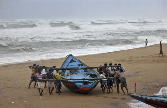 Fishermen move a fishing boat to a safer place along the shore ahead of cyclone Hudhud at Ganjam district in Odisha October 11, 2014. (Photo by Reuters/Stringer)