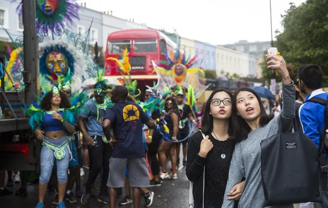 Two young women take a selfie by the parade at the Notting Hill Carnival on August 28, 2016 in London, England. (Photo by Jack Taylor/Getty Images)