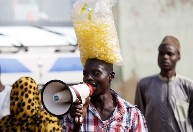 A man using a megaphone hawks local candy after Islamic prayers marking the Eid al-Adha festival, outside Kofar Mata district mosque in the city of Kano, Nigeria September 24, 2015. (Photo by Akintunde Akinleye/Reuters)