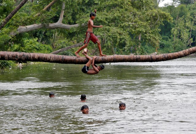 A boy prepares to jump from a fallen coconut tree into a lake on a hot summer day, amidst the outbreak of the coronavirus disease (COVID-19) in Kolkata, India, July 19, 2020. (Photo by Rupak De Chowdhuri/Reuters)