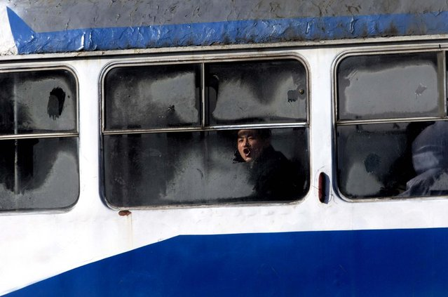 A man blows onto the frosted window of a tram in Pyongyang, North Korea, December 19, 2012. (Photo by Ng Han Guan/Associated Press)