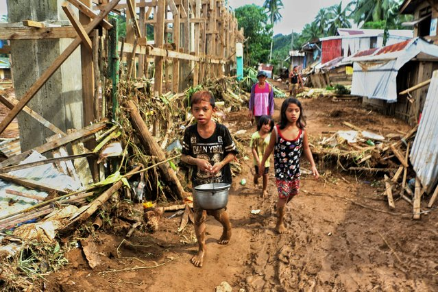 Children walk past debris and damaged houses trees in Barangay San Mateo Borongan in eastern Samar, Philippines on December 17, 2017, after Tropical Depression Kai-Tak blew through the area. Thousands of people heading home for Christmas in the Philippines were stranded on December 17 by Tropical Depression Kai-Tak, a day after the storm killed three people as it pounded the nation's eastern islands. (Photo by Alren Beronio/AFP Photo)