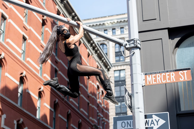 Natalie Duran, wearing a mask and dressed as Catwoman, climbs on street lights in SoHo as the city continues Phase 4 of re-opening following restrictions imposed to slow the spread of coronavirus on July 25, 2020 in New York City. The fourth phase allows outdoor arts and entertainment, sporting events without fans and media production. (Photo by Alexi Rosenfeld/Getty Images)