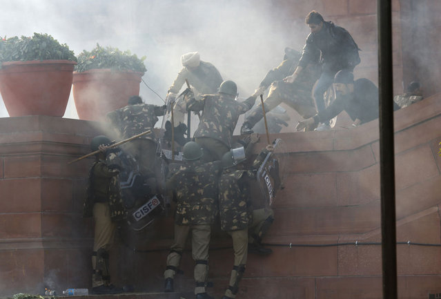 Police climb a wall as they are chased away by demonstrators during a protest rally near the presidential palace in New Delhi, on December 22, 2012. (Photo by Adnan Abidi/Reuters)