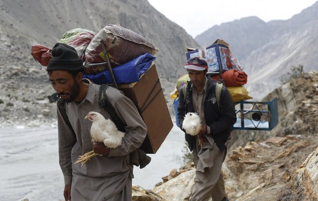 Porters carry live chickens, which serve as meat supplies, during a K2 base camp trek in the Karakoram mountain range in Pakistan August 28, 2014. (Photo by Wolfgang Rattay/Reuters)