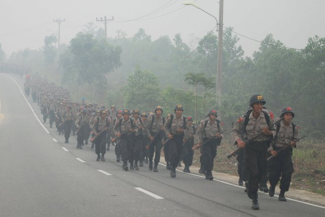 "Students of State Police School (SPN) run amid haze while attending a physical exercise in Pekanbaru, Indonesia Riau province, September 30, 2015 in this picture taken by Antara Foto. Indonesia has sent nearly 21,000 personnel to fight forest fires raging in its northern islands, the disaster management agency said on Tuesday, but smoke cloaks much of the region with pollution readings in the ""very unhealthy"" region in neighbouring Singapore. (Photo by Rony Muharrman/Reuters/Antara Foto)"