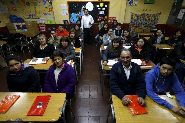 Teacher Guillermo Valenzuela poses for a picture with students of primary grade who are attending a night school for adults at Laura Vicuna school, in a popular neighbourhood of Santiago, September 10, 2015. (Photo by Ivan Alvarado/Reuters)