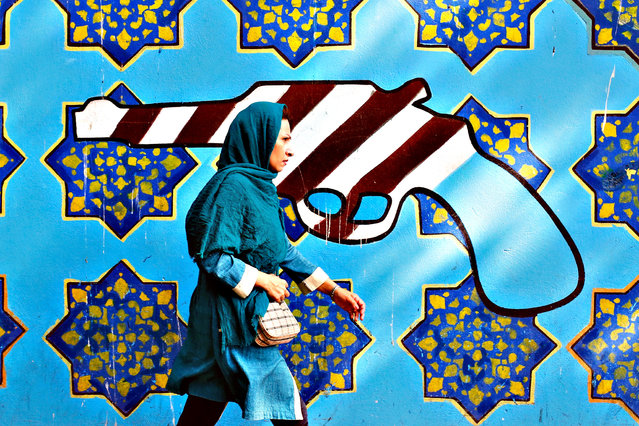 An Iranian woman walks past a painting of a revolver, painted in an American-flag style, on the wall of former US embassy in Tehran, Iran, 02 September 2015. (Photo by Abedin Taherkenareh/EPA)