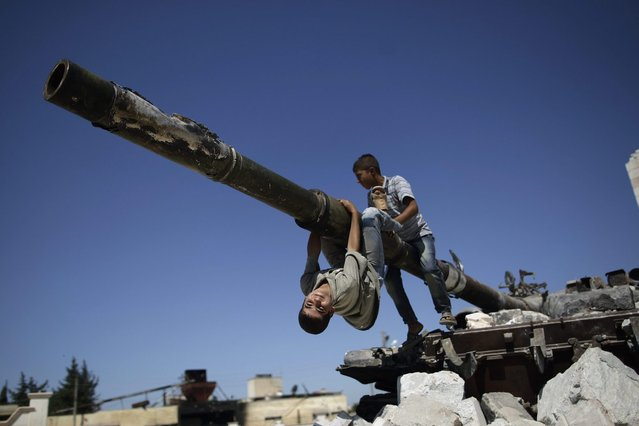 A  boy looks back while he and another boy play on a Syrian military tank, destroyed during fighting with the Rebels, in the Syrian town of Azaz, on the outskirts of Aleppo, Sunday, September 2, 2012. (Photo by Muhammed Muheisen/AP Photo)