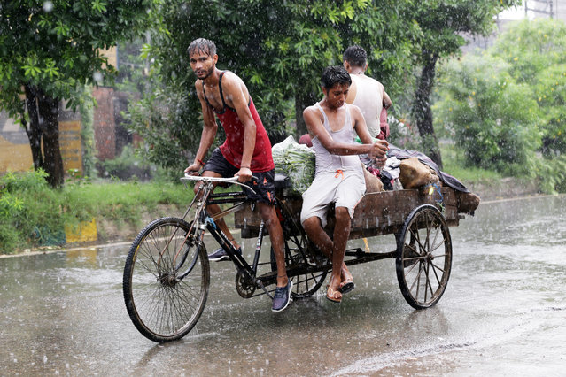 Indian men ride on a cycle cart during a spell of heavy rain in Amritsar, India, 14 August 2020. The monsoon season in India normally sta​​rts in the beginning of June and ends in September. (Photo by Raminder Pal Singh/EPA/EFE)