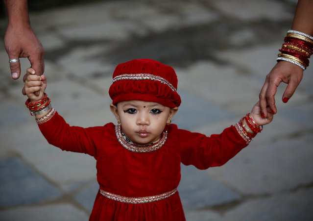 A young girl, holding the hands of her parents, pouts while being photographed during the Kumari Puja festival in Kathmandu, Nepal September 14, 2016. (Photo by Navesh Chitrakar/Reuters)