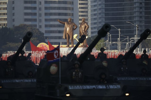 Statues of Kim Il Sung and Kim Jong Il stand above soldiers during a military parade in Pyongyang, North Korea, Saturday, October 10, 2015. North Korean leader Kim Jong Un declared Saturday that his country was ready to stand up to any threat posed by the United States as he spoke at a lavish military parade to mark the 70th anniversary of the North's ruling party and trumpet his third-generation leadership. (Photo by Wong Maye-E/AP Photo)