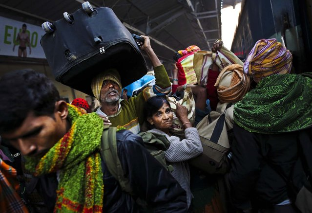 Passengers crowd together on a train platform where a stampede took pace a night before in Allahabad, India on February 11, 2013.The death toll from a stampede in a train station rose to 36 where millions of devotees had gathered for a Hindu festival. (Photo by Kevin Frayer/Associated Press)
