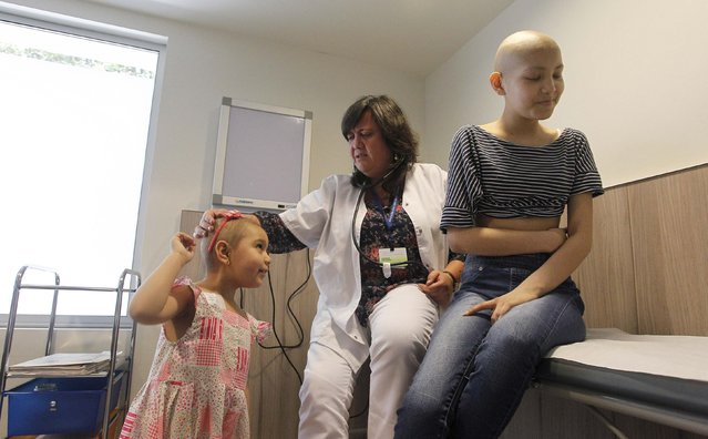 Oncologist Katherine Kopp (C) speaks with her patients Alexandra Munoz (L), 5, and Isidora Serrano, 14, who lost their hair due to chemotherapy to treat their cancers, in the cancer ward of the Luis Calvo Mackenna Hospital in Santiago, October 20, 2014. (Photo by Rodrigo Garrido/Reuters)