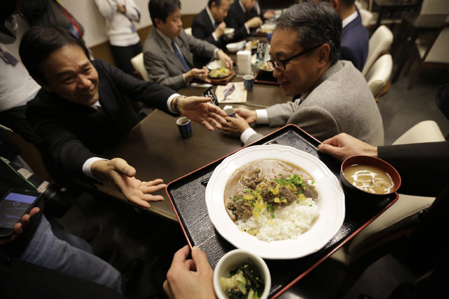 A man serves a curry dish with whale meat to one of lawmakers and government officials who promote whale meat at a dining room of Ministry of International Trade and Industry in Tokyo Wednesday, November 19, 2014. Japan has slashed its whale catch target in the Antarctic by two-thirds in a bid to resume its annual whale hunt, which an international court ruled must stop. (Photo by /Eugene Hoshiko/AP Phot)