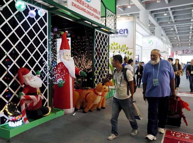 Men walk past a booth displaying Christmas lights decorated with Santa Claus dolls at the China Import and Export Fair, also known as Canton Fair, in the southern Chinese city of Guangzhou October 15, 2015. (Photo by Bobby Yip/Reuters)