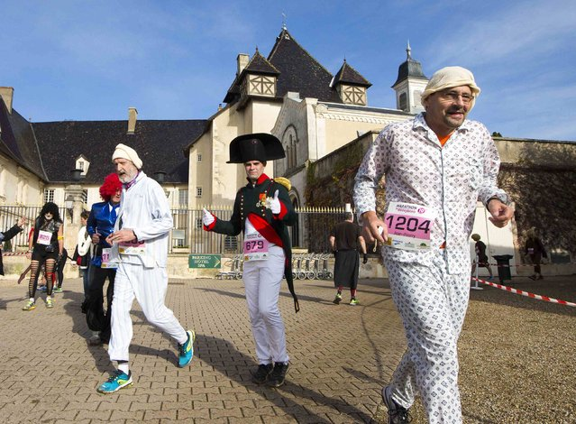 Costumed competitors, including a man dressed as Napoleon, run during the Marathon International du Beaujolais race at the castle of Pizay, November 22, 2014. (Photo by Robert Pratta/Reuters)