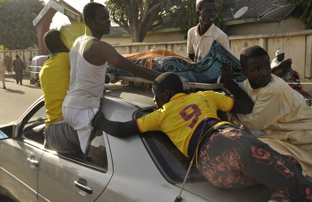 The remains of the Kano central mosque bombing victim is carried on the top of a car from the Murtala Mohammed specialist Hospital for burial according to Muslim rites, in Kano State, November 28, 2014. Gunmen set off three bombs and opened fire on worshippers at the central mosque in north Nigeria's biggest city Kano, killing at least 35 people on Friday, witnesses and police said, in an attack that bore the hallmarks of Islamist Boko Haram militants. (Photo by Reuters/Stringer)