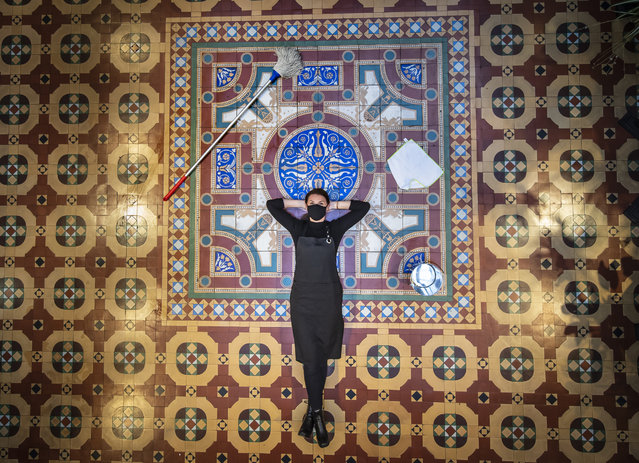 Bar Convent employee Lauren Masterman relaxes after cleaning a historic George and Arthur Maw tiled floor created in 1867, one of only two surviving examples of this assemblage of tiles, at England's oldest living convent Bar Convent on October 13, 2020. Visitors to the convent are being invited to follow in the footsteps of residents from the last 150 years and enjoy the historic space decorated with rare 19th century floor tiles. (Photo by Danny Lawson/PA Images via Getty Images)