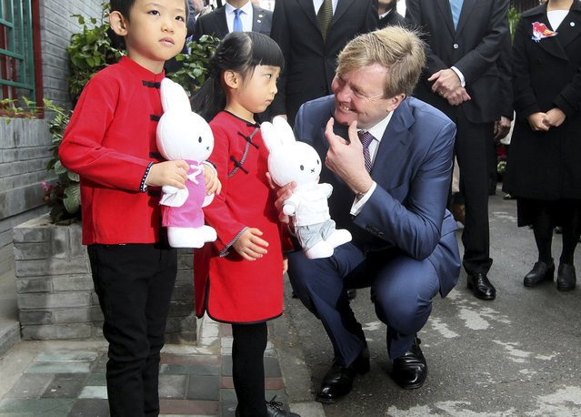 Netherlands' King Willem-Alexander (R) gestures to a girl as he visits a hutong, or small alley, at the Qianmen area in Beijing, China, October 26, 2015. (Photo by Reuters/Stringer)