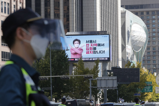 """An electric screen shows a ban on rallies as a South Korean police officer wearing a face mask and face shield stands guard to block protesters' possible rallies against the government in Seoul, South Korea, Friday, October 9, 2020. Seoul city temporarily banned outdoor rallies with 10 or more people over infection risks against the spread of the coronavirus. The Korean letters read: """"Prohibition of rallies across the Seoul city"""". (Photo by Ahn Young-joon/AP Photo)"""