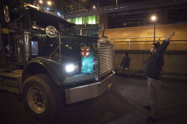 A protester stands in front of a truck to block Lincoln Tunnel during a demonstration against the grand jury decision not to indict the police officer in the death of Eric Garner, in the Manhattan neighborhood of New York December 3, 2014. A New York City grand jury decided not to charge a white police officer in the chokehold death of Garner, an unarmed black man, sparking outrage and protests on Wednesday, and the U.S. Justice Department said it would investigate the incident. (Photo by Carlo Allegri/Reuters)